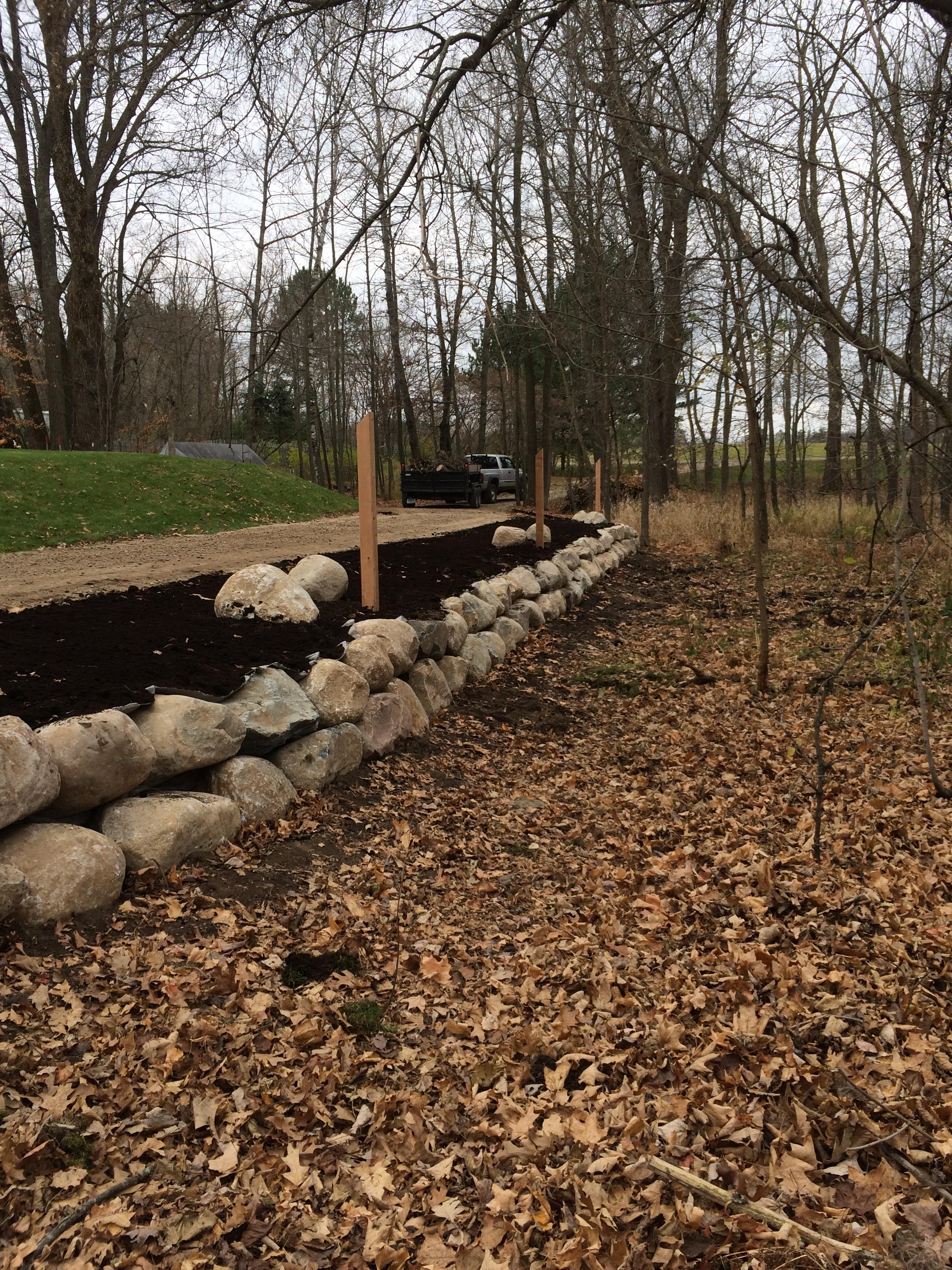 boulder retaining wall along driveway