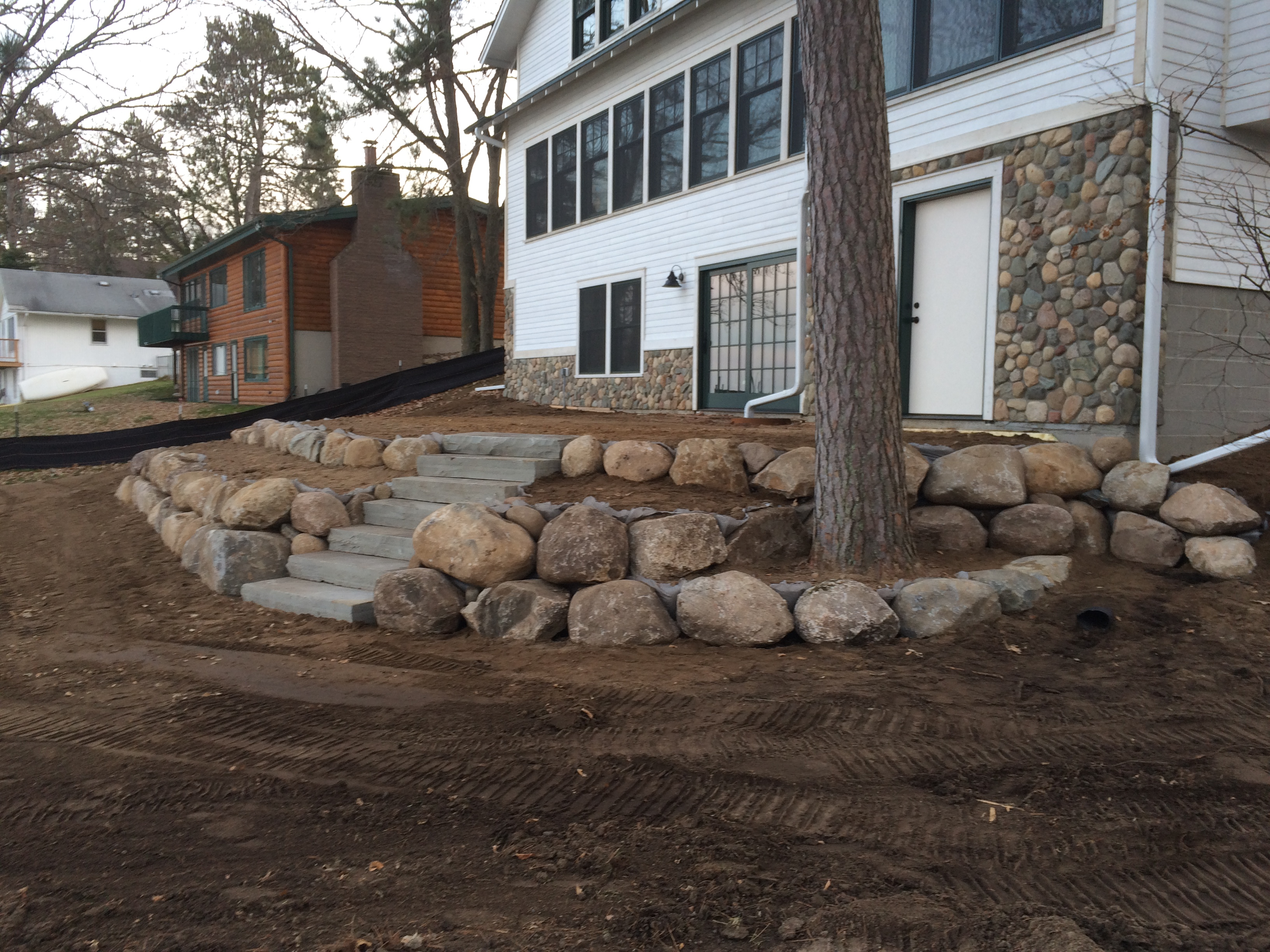 boulder retaining wall on lakefront house
